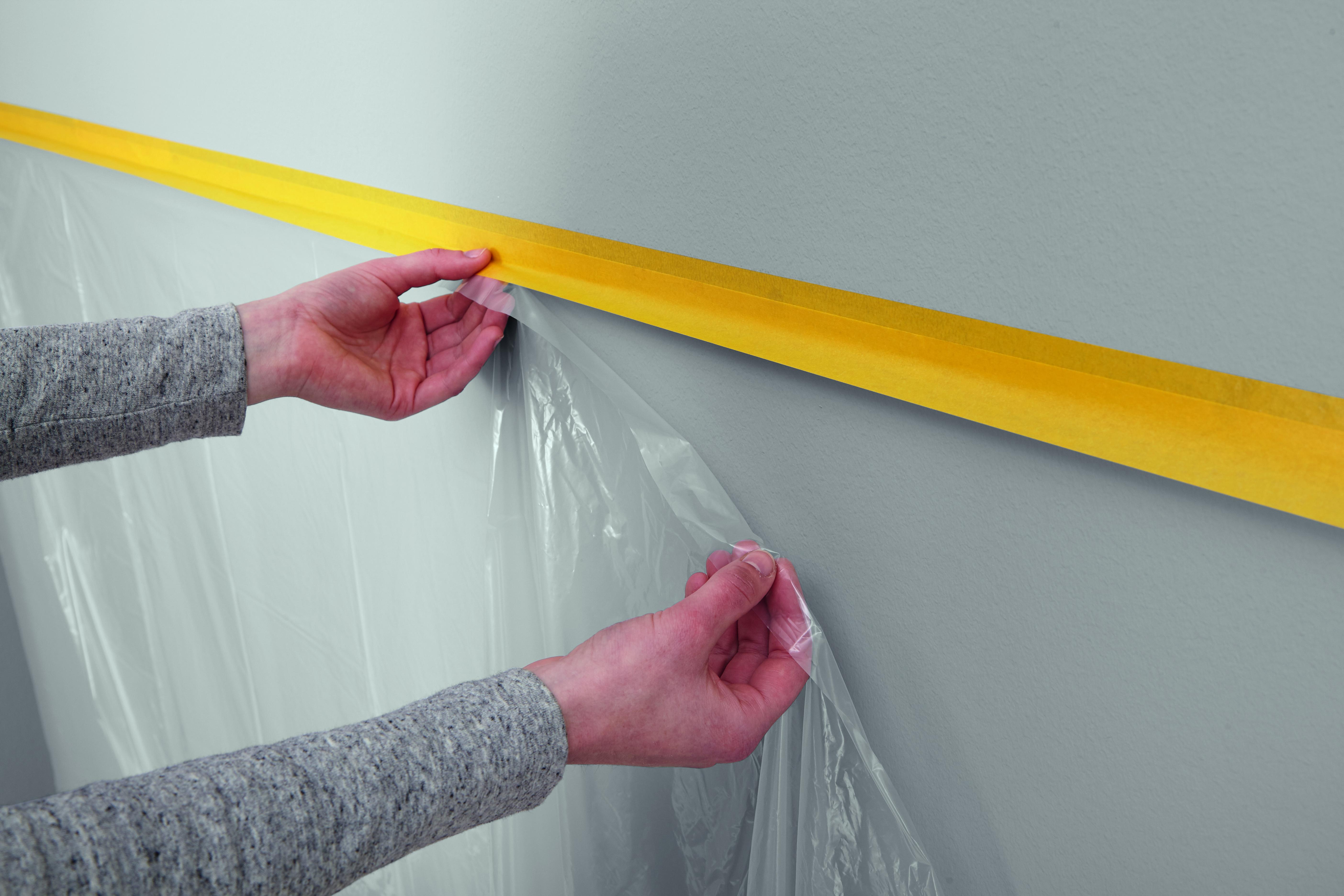 Eine Malerfolie An Den Zur Hälfte Abstehenden Klebestreifen Kleben. Diese  Folie Wird In Den Folgenden Schritten Die Wand Vor Farbspritzern Schützen.