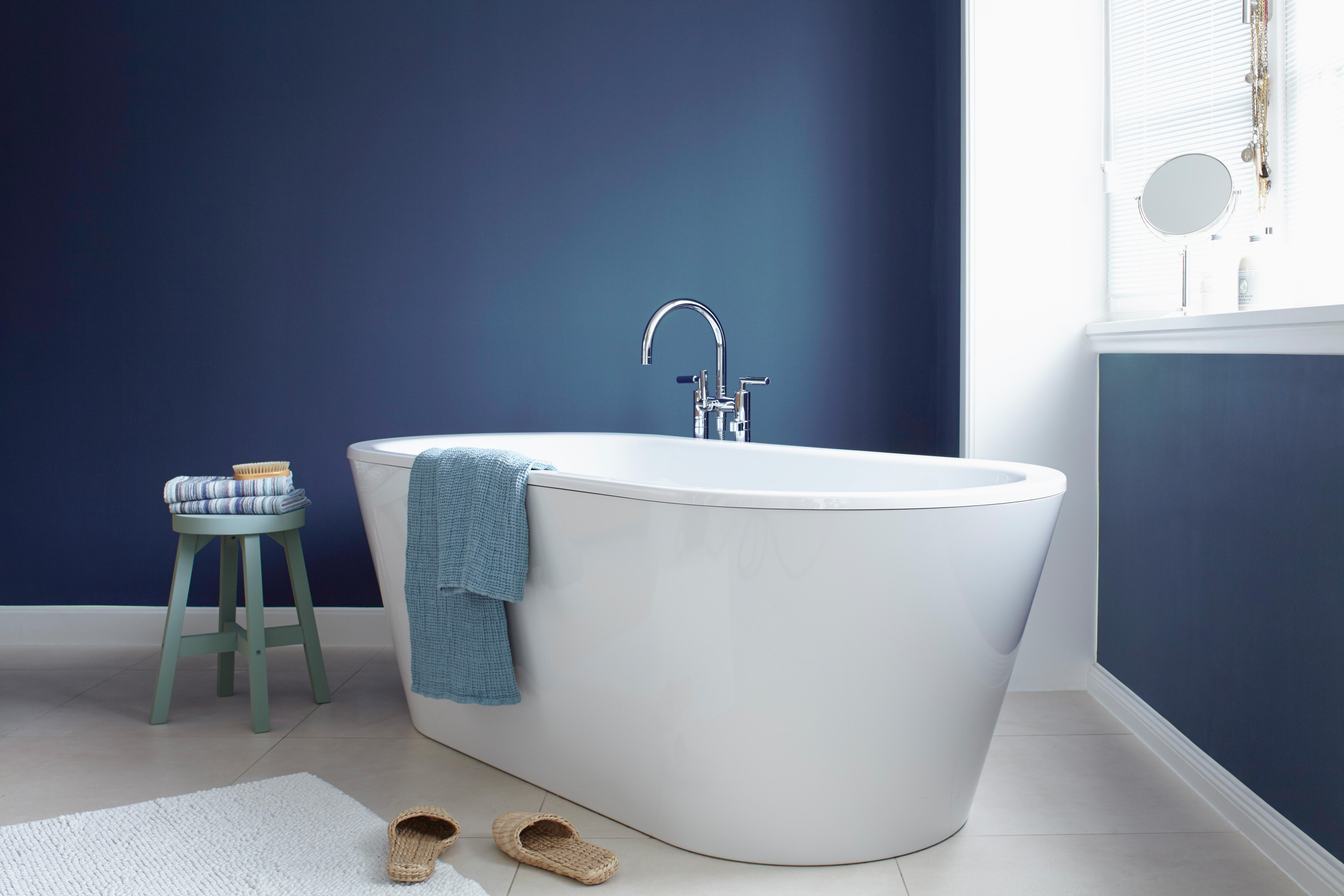 Weißes, Modernes Badezimmer Mit Freistehender Badewanne Und Dunkel Blauer  Wand In Der Alpina Farbe Blaue
