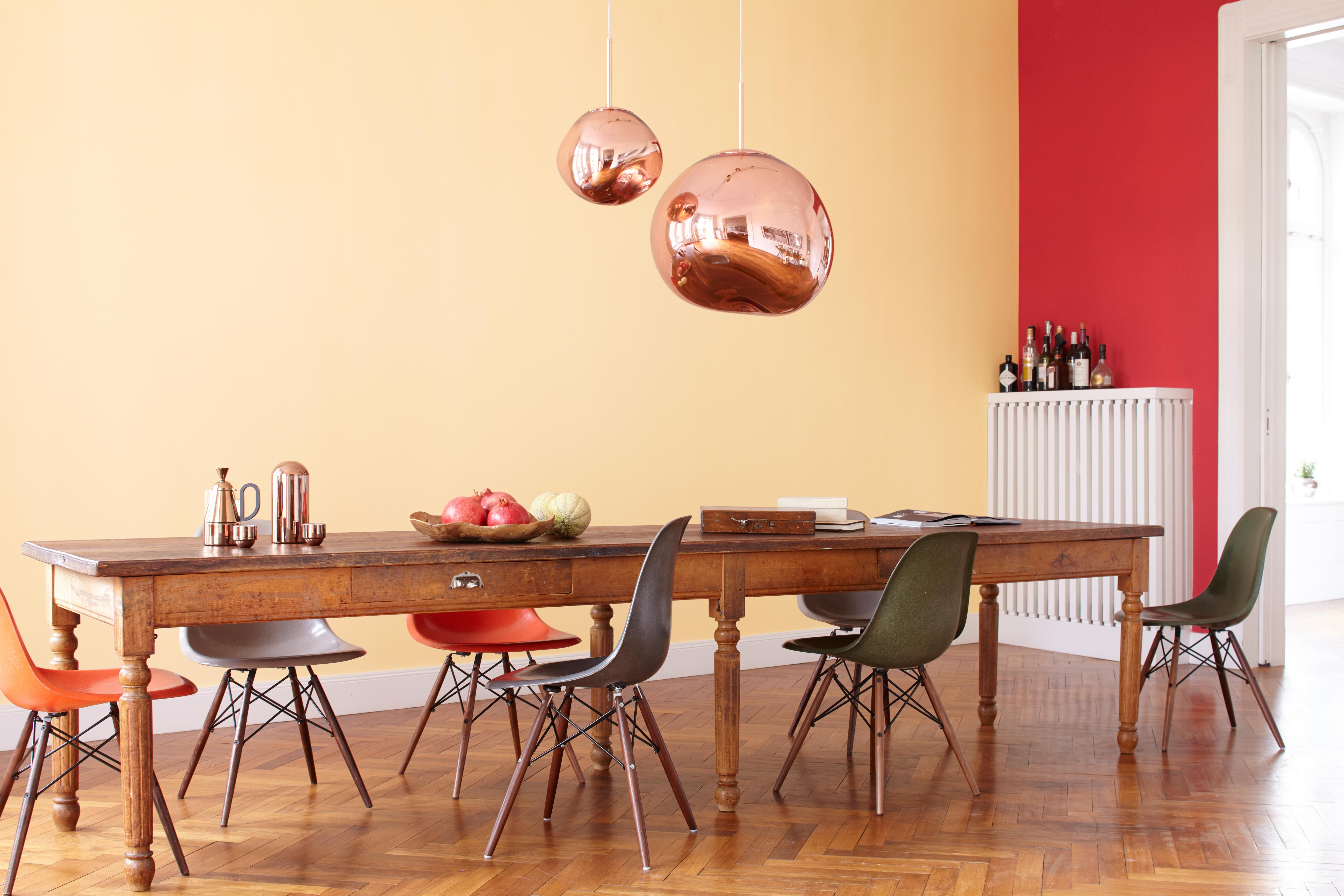 Warmes, Gemütliches Esszimmer Mit Holztisch Und Messinglampen Vor Einer  Orange Roten Wand In Der Alpina
